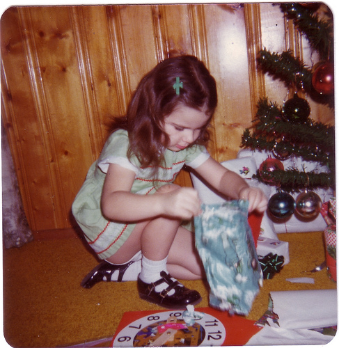 young girl opening christmas presents