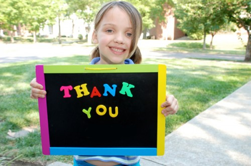 child holding thank you sign