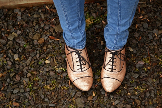 lace up flat shoes shown against gravel