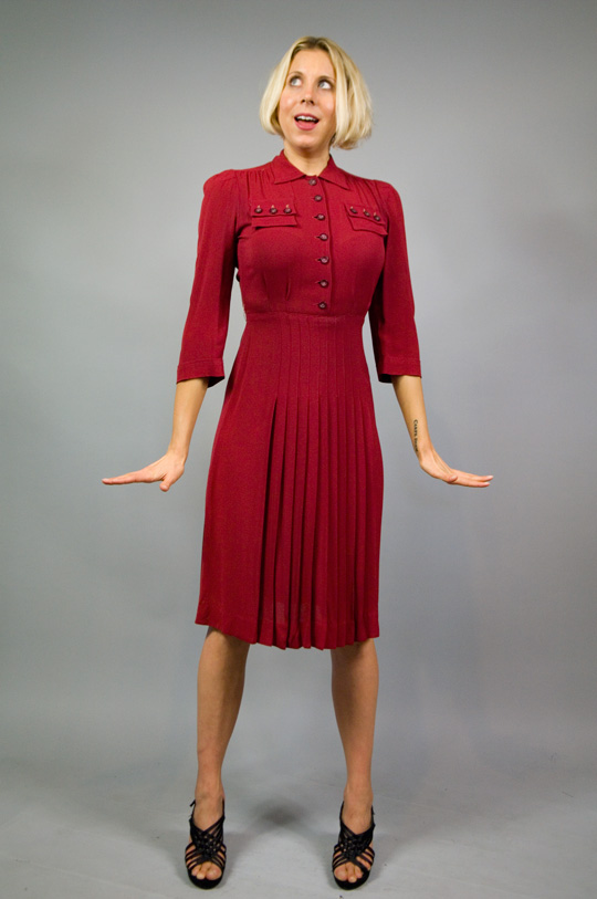 model wearing a 1940s red military dress