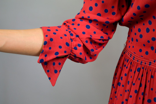 the sleeve and cuffs of a 1940s red polka dot rayon dress