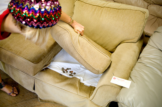 girl with a sequin beret finds money under the cushion of a couch in a thrift store