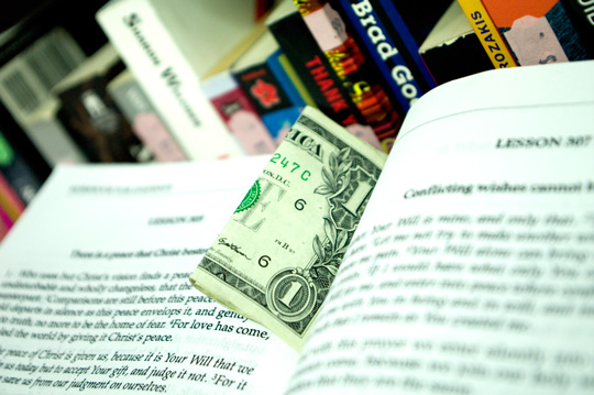 a dollar bill caught between the pages of a course in miracles book