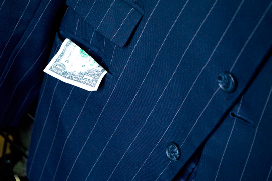a dollar bill hanging out of a men's blazer pocket