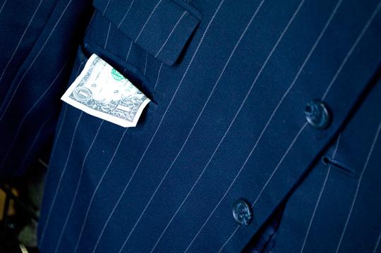 a dollar bill hanging out of a men's blazer pocket
