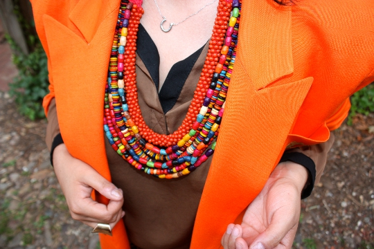 a layered necklace worn with an orange vintage 1980s blazer