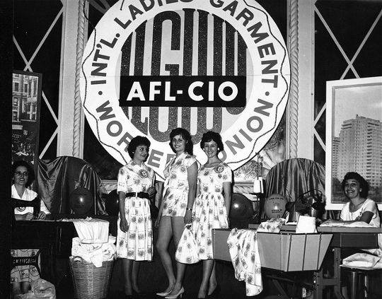 union workers in 1950s standing in front of clothing union tag from the 1950s