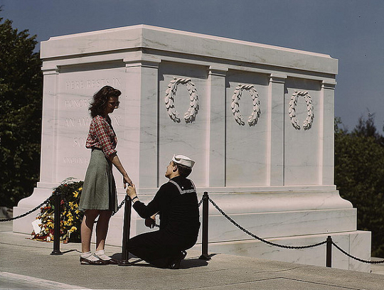 girl wearing a pencil skirt as soldier kneels before her
