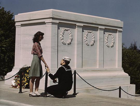 girl wearing a pencil skirt as soldier kneels before her