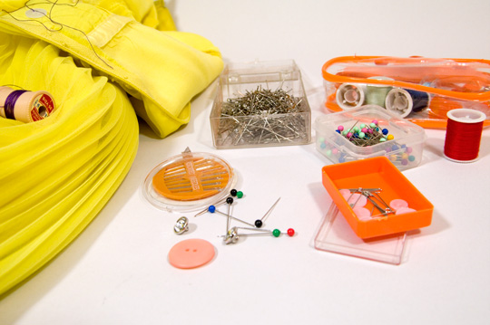 an array of sewing supplies including thread, needles, pins and safety pins