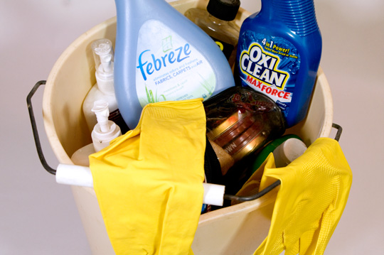 a bucket full of cleaning supplies like febreze oxi clean and yellow cleaning gloves