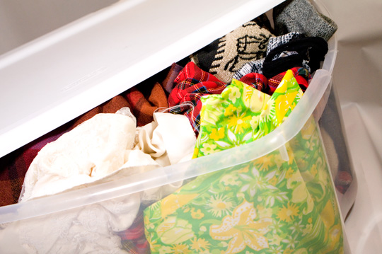 a plastic storage bin full of colorful vintage clothing