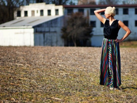 a young woman wearing a vintage skirt in a field