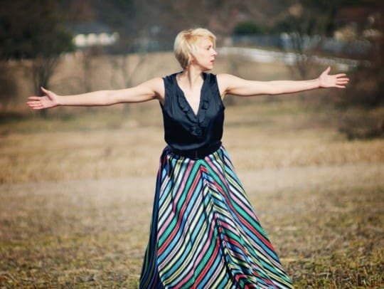 woman wears a vintage style striped skirt in a field