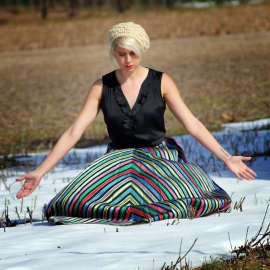 a woman wears a vintage striped skirt in a field