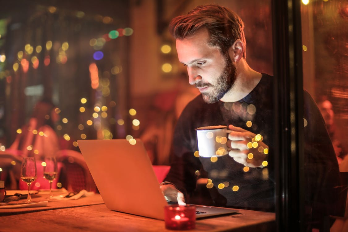 Man Holding Mug in Front of Laptop